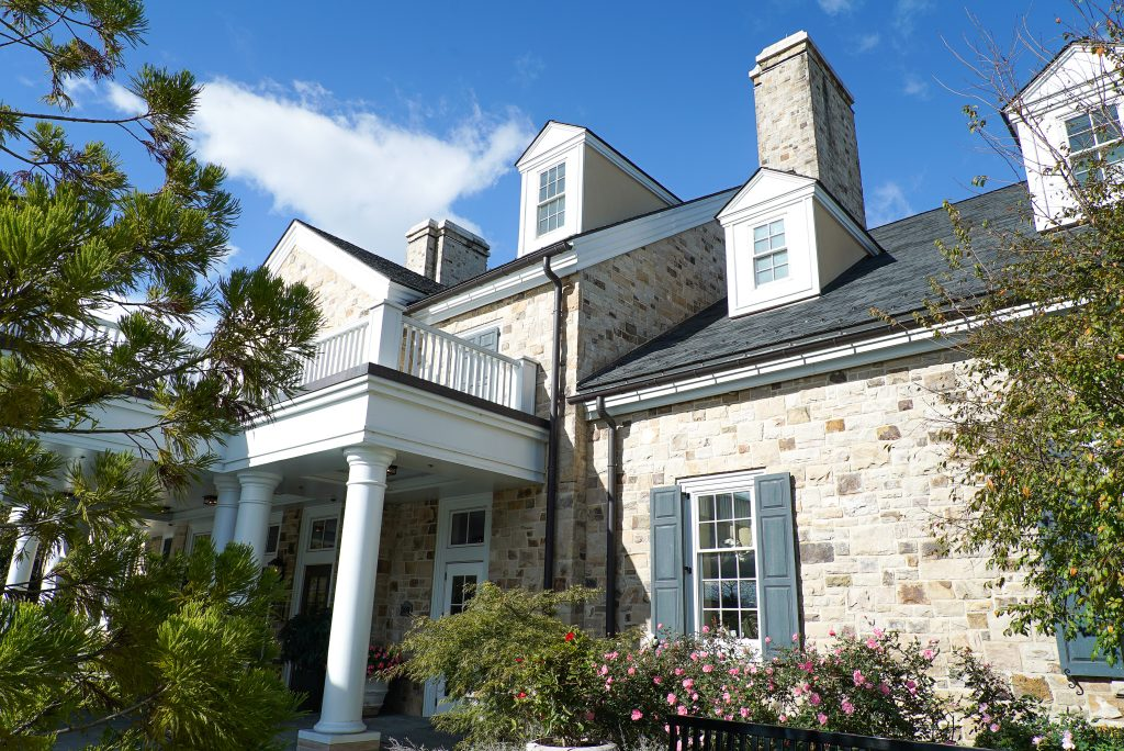 Stone inn with white columns and blue sky- Ultimate Virginia Wine Country Guide