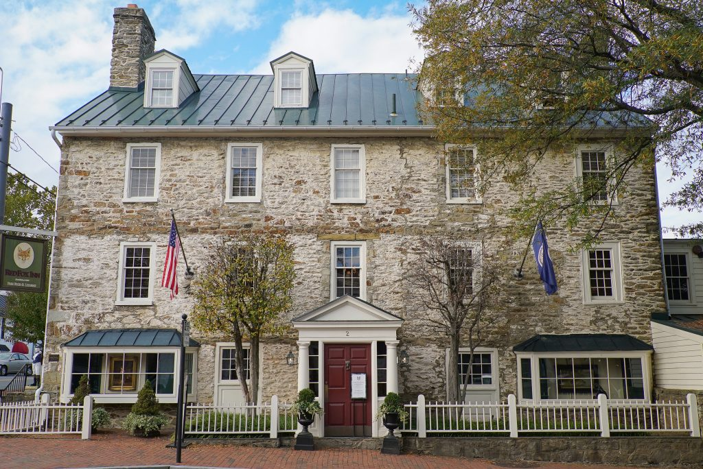Stone inn with red door and green trees in Middleburg Virginia- Ultimate Virginia Wine Country Guide