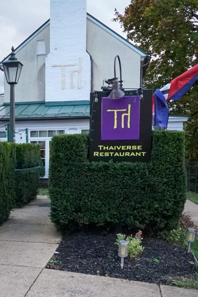 Purple sign saying Thaiverse Restaurant with green hedges behind the sign
