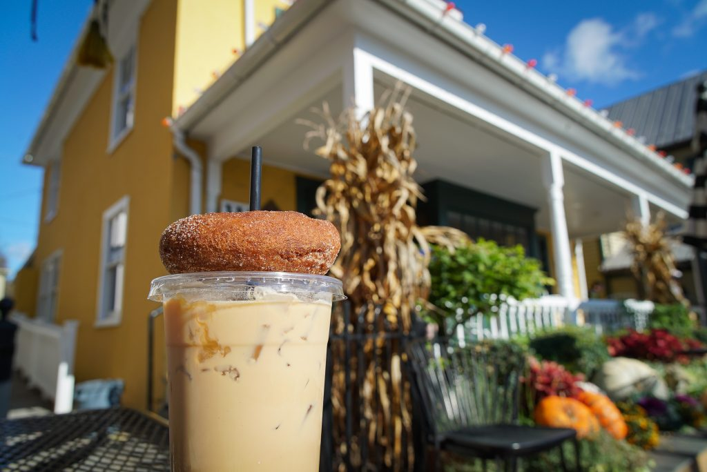 Iced coffee and donut with coffee shop in the background