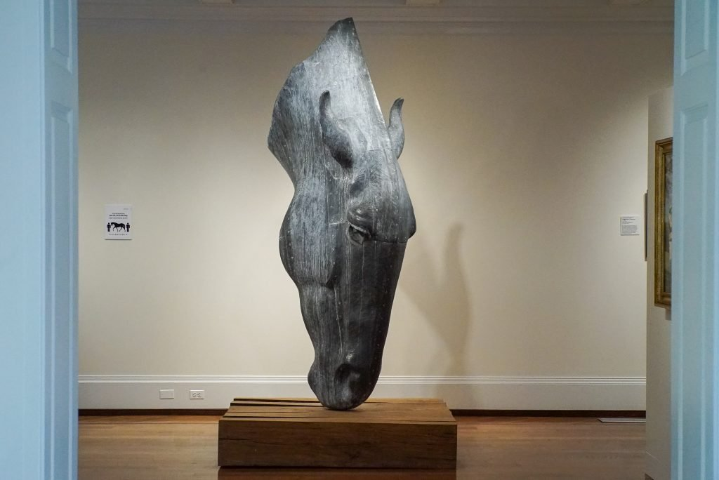 Sculpture of a horse head with the nose touching the ground - National Sporting Museum