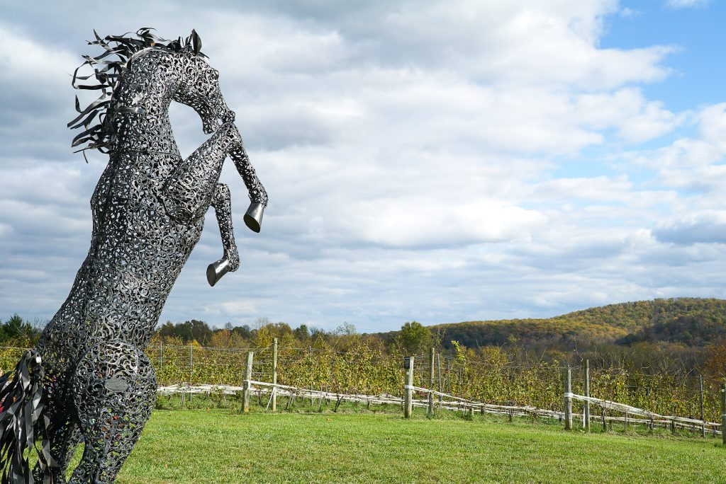 Metal statue of a horse on its hind legs with vineyards, clouds, and mountains in the background - 50 West Winery in Middleburg Virginia