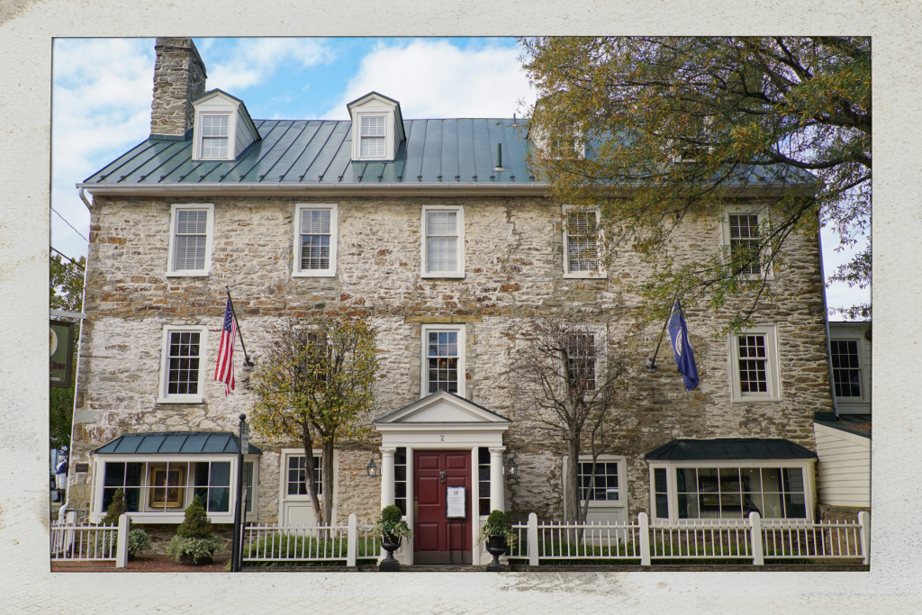 Stone Inn with red door and blue sky in the background - one of the best places to stay in Middleburg Virginia