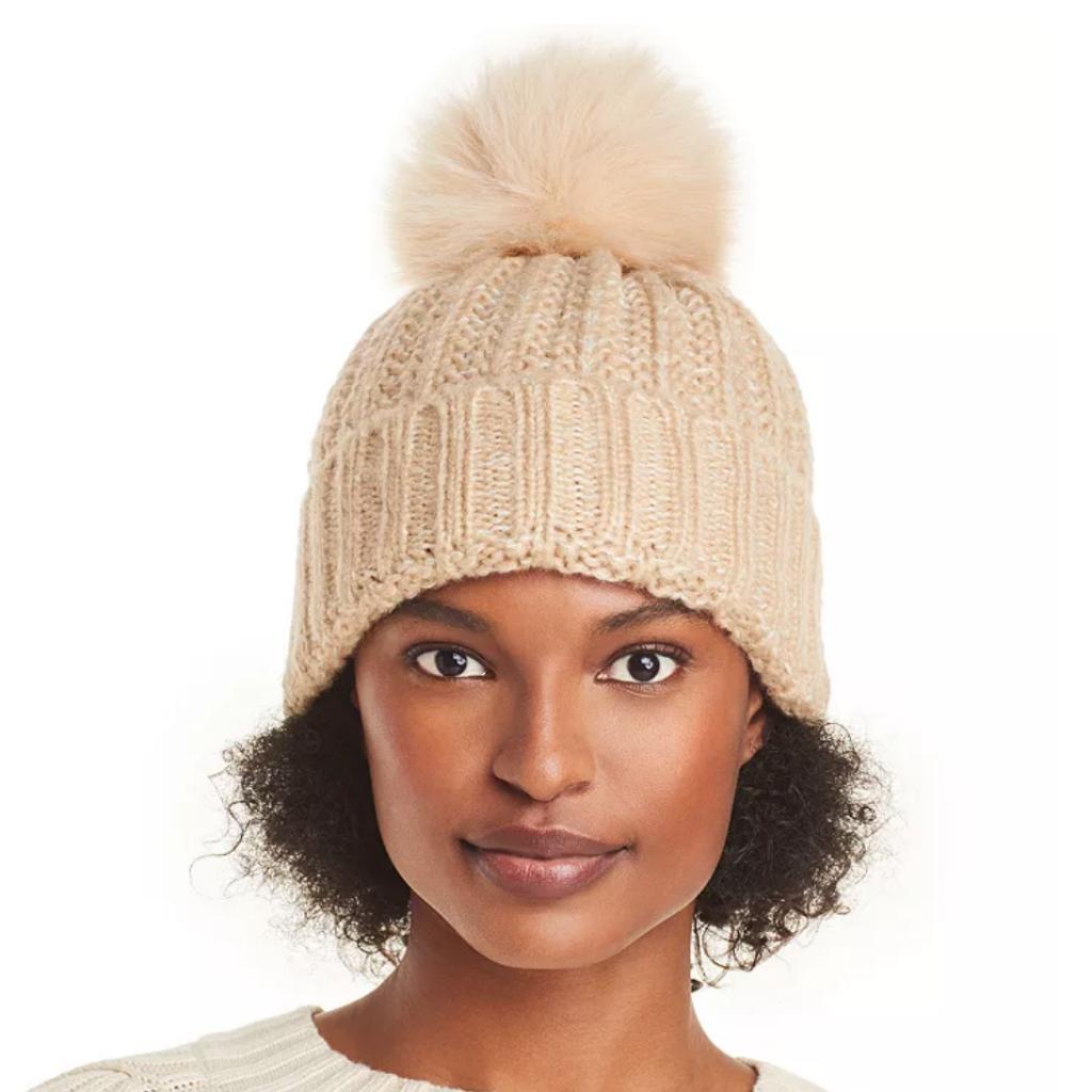 Woman wearing tan hat with pom pom