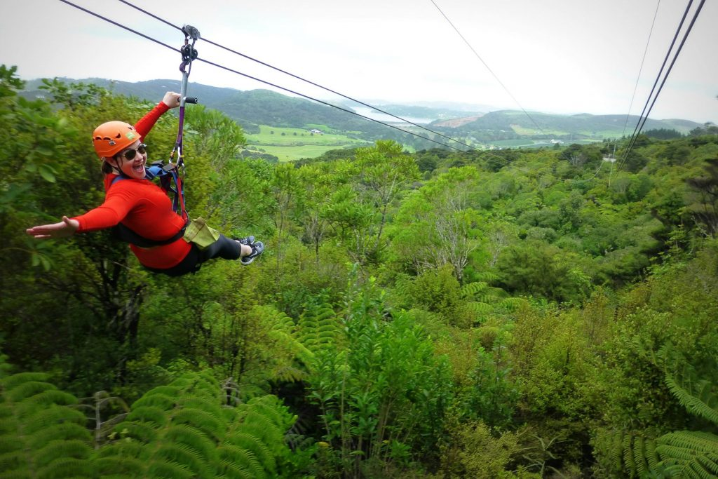 Woman in red ziplining over green forest - Ultimate Auckland New Zealand Guide